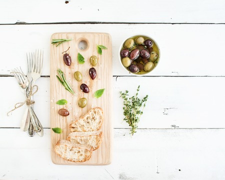 Mediterranean olives with herbs and ciabatta slices on rustic wooden board  over white wooden background, top view, copy space 版權商用圖片
