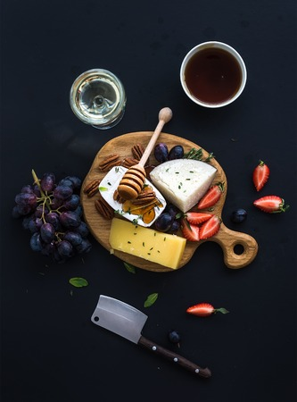 whine: Cheese appetizer selection or whine snack set. Variety of cheese, grapes, pecan nuts, strawberry and honey on round wooden board over black backdrop, top view Stock Photo