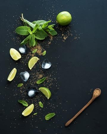 モヒートの材料。新鮮なミント、ライム、氷、砂糖黒の背景で。コピー スペース平面図