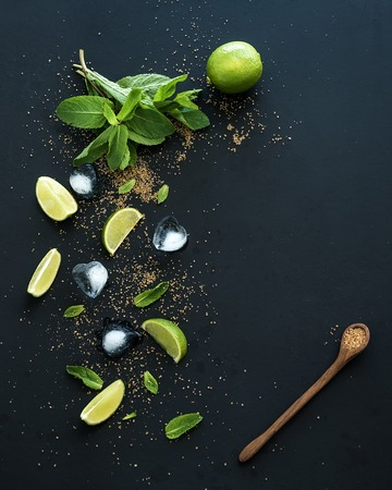 vintage leaf: Ingredients for mojito. Fresh mint, limes, ice, sugar over black backdrop. Top view, copy space