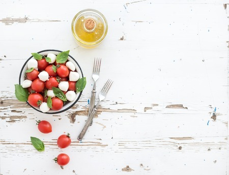 fresh vegetable: Caprese salad: cherry-tomatoes and mozzarella in metal bowl witholive oil on rustic white wooden backdrop, top view, copy space Stock Photo