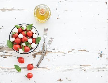 marco madera: Ensalada Caprese: cereza-tomates y mozzarella en un taz�n de metal aceite witholive en r�stica tel�n de fondo de madera blanca, vista desde arriba, copia espacio