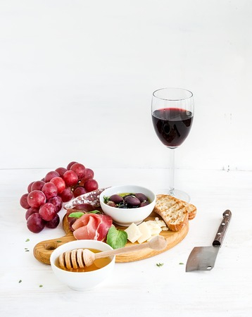 Wine appetizer set. Glass of red wine, grapes, honey, parmesan cheese, meat variety, bread slices, pecan nuts, honey, olives and basil on rustic wooden board over white wood backdrop