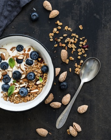 cereal: Healthy breakfast. Oat granola with fresh blueberries, almond, yogurt and mint in a rustic metal bowl over dark grunge surface. Top view Stock Photo