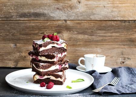 Brownies-cheesecake toren met frambozen op een witte keramische plaat, houten achtergrond, kopieer ruimte
