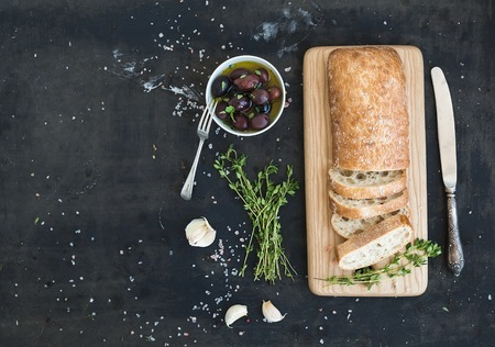 Italian ciabatta bread cut in slices on wooden chopping board with herbs, garlic and olives over dark grunge backdrop, copy space, top view Stock Photo