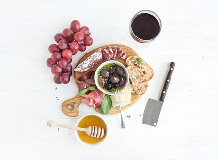 top: Wine appetizer set. Glass of red wine, grapes, honey, parmesan cheese, meat variety, bread slices, pecan nuts, honey, olives and basil on rustic wooden board over white wood backdrop, top view