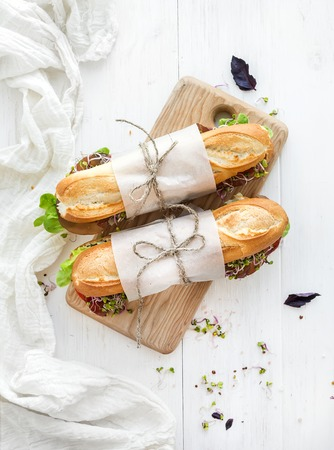 Sandwiches with beef, fresh vegetables and herbs on rustic wooden chopping board over white wood backdrop, top view