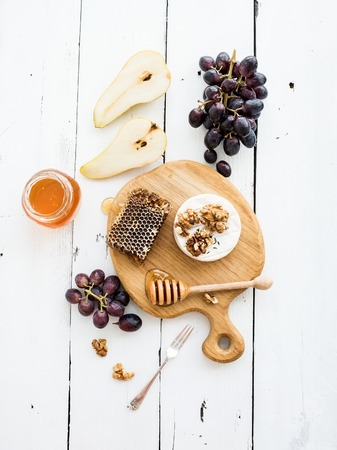 vine pear: Camembert cheese with grape, walnuts, pear and honey on oak serving board over white rustic wood backdrop, top view copy space