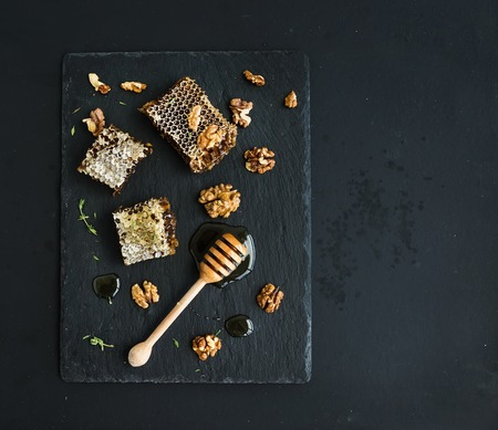 Honeycomb, walnuts and honey dipper on black slate tray over grunge dark backdrop, top view, copy space