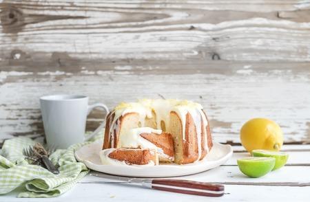 Moist lime and lemon bundt yogurt cake, white rustic wooden  . Shallow depth of field. Stock Photo