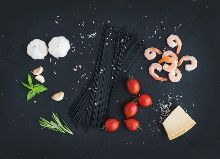spaghetti dinner: Ingredients for black pasta with seafood. Shrimps, spaghetti, basil, garlic, spices, parmesan cheese and  cherry-tomatoes on dark grunge backdrop, top view,