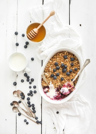 yogurt: Healthy breakfast. Oat granola berry crumble with fresh blueberries, yogurt and honey in ceramic cooking dish over white rustic backdrop, top view Stock Photo