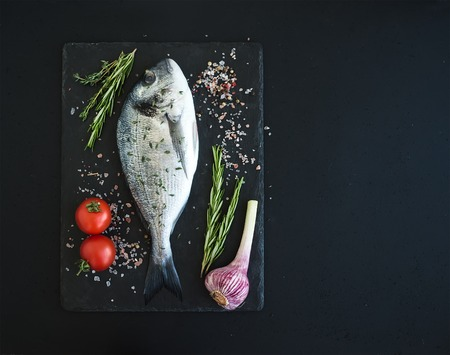 Fresh uncooked dorado or sea bream fish with vegetables, herbs and spices on black slate tray over dark grunge backdrop, top view, copy space Stock Photo