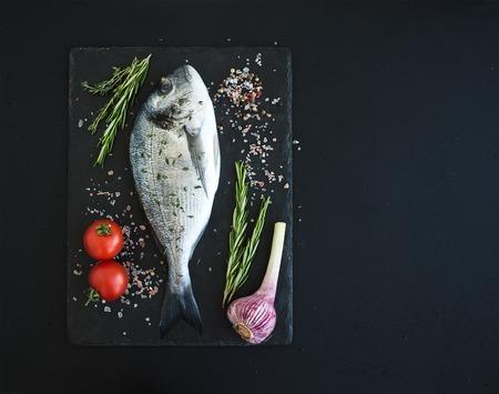 Verse ongekookte dorado of zeebrasem vis met groenten, kruiden en specerijen op zwarte lei tray over dark grunge achtergrond, bovenaanzicht, kopieer ruimte Stockfoto