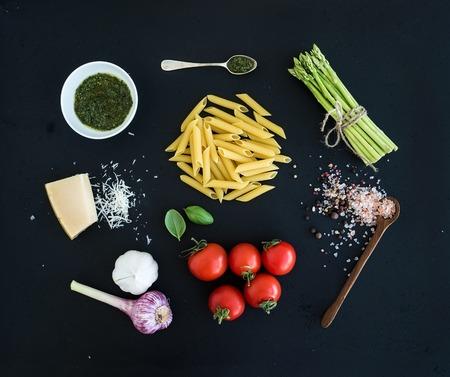 Ingrediënten voor het koken van pasta. Penne, groene asperges, basilicum, pesto saus, knoflook, kruiden, Parmezaanse kaas en cherry-tomaten op donkere grunge achtergrond, bovenaanzicht