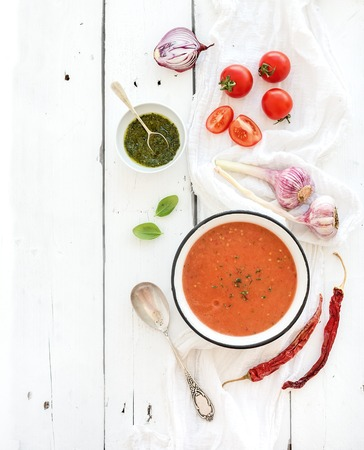 Gazpacho soup in rustic metal bowl with fresh tomatoes, green sauce, chili, garlic and basil over rustic white wooden backdrop. Top view, copy space Stok Fotoğraf
