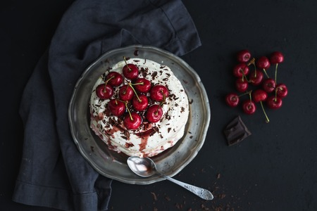 Pavlova cake with fresh cherry, cheese cream and chocolate chips in vintage silver plate over dark grunge , top view, copy space Stok Fotoğraf