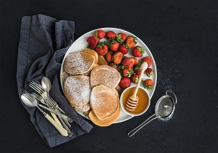 grunge silverware: Breakfast plate. Homemade pancakes with fresh strawberry and honey, kitchen napkin, vintage silverware on dark grunge . Top view, copy space