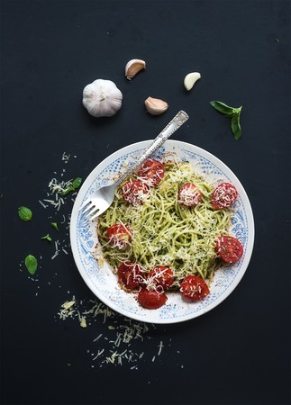 italy food: Pasta spaghetti with pesto sauce, basil, garlic, baked cherry-tomatoes on rustic dark table, top view, copy space
