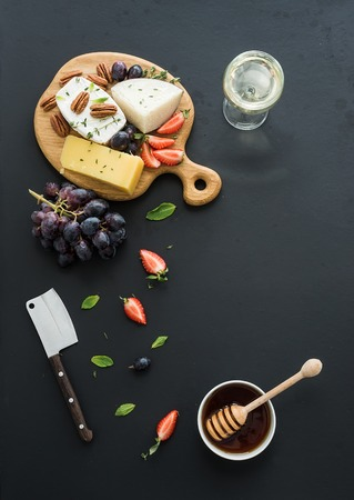 food and wine: Cheese appetizer selection or whine snack set. Variety of cheese, grapes, pecan nuts, strawberry and honey on round wooden board over black backdrop, top view, copy space