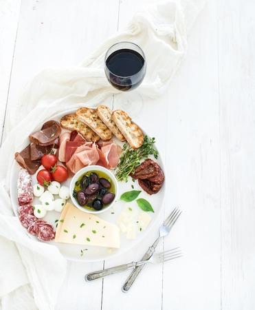 와인 전채 설정합니다. 체리 토마토, 흰색 나무 배경, 상위 뷰를 통해 라운드 세라믹 접시에 치즈 치즈, 고기, 다양한 빵 조각, 말린 토마토, 올리브, 바