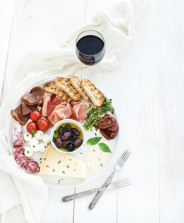 Wine appetizer set. Cherry-tomatoes, parmesan cheese, meat variety, bread slices, dried tomatoes, olives and basil on round ceramic plate over white wood backdrop, top view, copy space