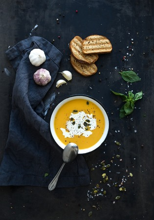 Pumpkin soup with cream, seeds, bread and fresh basil in rustic metal plate on grunge black . Top view Banque d'images