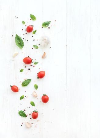 Kersentomaten, verse basilicumbladeren, knoflookkruidnagels en kruiden op rustieke witte houten achtergrond, hoogste mening, exemplaarruimte