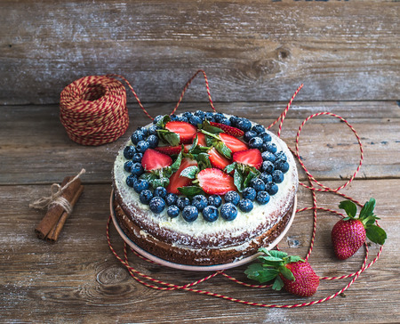 cakes background: Rustic spicy ginger cake with cream-cheese filling, fresh strawberries and blueberries over a rough wood background with a decorative rope