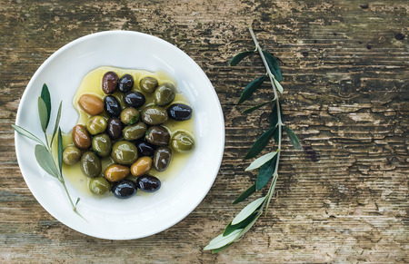 A plate of Mediterranean olives in oil with branch of olive tree. Top view, copy space