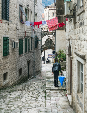 strangers: Kotor, Montenegro, Balkans, 24.01.2015. Narrow paved street of the old town of Kotor and the strangers walking down it