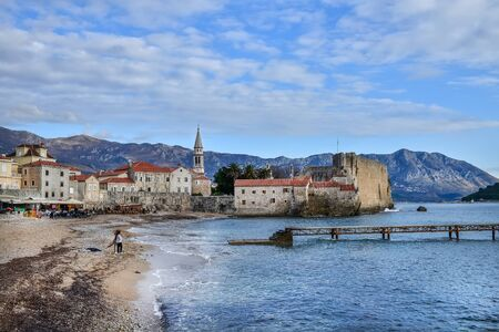 balkan peninsula: Budva, Montenegro, Balkan Peninsula, 25.01.2015. Budva beach near old town wall and fortress in winter season. People sitting in a cafe, children playing near the sea Editorial