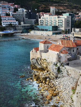 balkan peninsula: Budva, Montenegro, Balkan Peninsula, 25.01.2015. View over the old town buildings on a cliff, beach and hotel from the top of the ancient citadel in Budva on a clear winter day Editorial