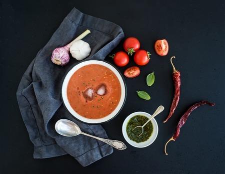 신선한 토마토, 녹색 소스, 고추, 마늘, 바 질 어두운 그런 지 배경 위에 소박한 금속 그릇에 가스 파초 수프. 평면도 스톡 콘텐츠