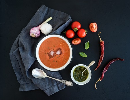 Gazpacho soup in rustic metal bowl with fresh tomatoes, green sauce, chili, garlic and basil over dark grunge backdrop. Top view