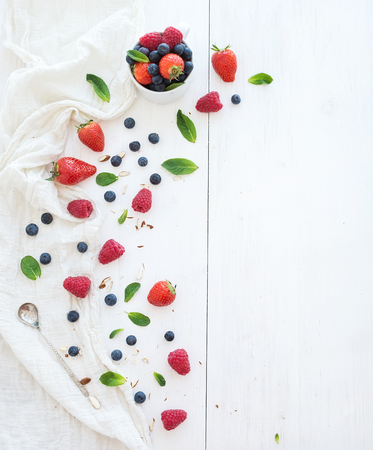 raspberries: Berry frame with copy space on right. Strawberries, raspberries, blueberries and mint leaves, white wooden background, top view