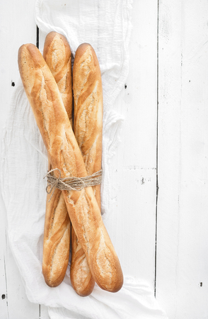 homemade bread: Freshly baked French baguettes on white wooden table. Top view, copy space Stock Photo