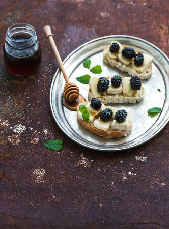 blue grunge background: Italian bruschetta sandwich with brie cheese, honey and blackberry on vintage silver tray over grunge rusty metal background, top view, copy space