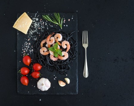 spaghetti sauce: Black pasta spaghetti with shrimps, basil, pesto sauce, garlic, parmesan cheese and cherry-tomatoes on a slate tray over black grunge backdrop, top view, copy space