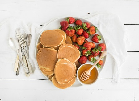 golden honey: Breakfast plate. Homemade pancakes with fresh strawberry and honey, kitchen napkin, vintage silverware on rustic white background. Top view. Stock Photo