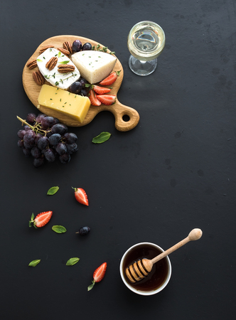 whine: Cheese appetizer selection or whine snack set. Variety of cheese, grapes, pecan nuts, strawberry and honey on round wooden board over black backdrop, top view, copy space