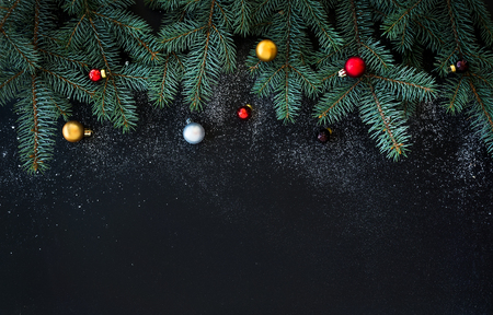 Christmas or New Year decoration background: fur-tree branches, colorful glass balls  on black grunge background with copy space