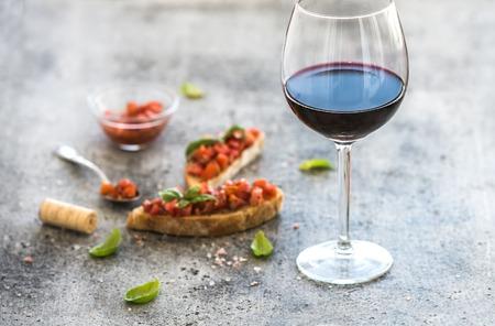 alimentos y bebidas: establece aperitivo vino. Vaso de vino tinto, brushettas con tomate fresco y albahaca en más de telón de fondo gris grunge rústico
