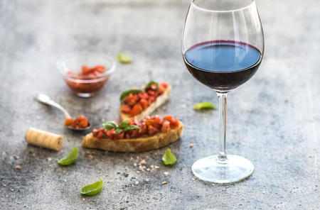 legumbres secas: Wine appetizer set. Glass of red wine, brushettas with fresh tomato and basil on over rustic grunge grey backdrop