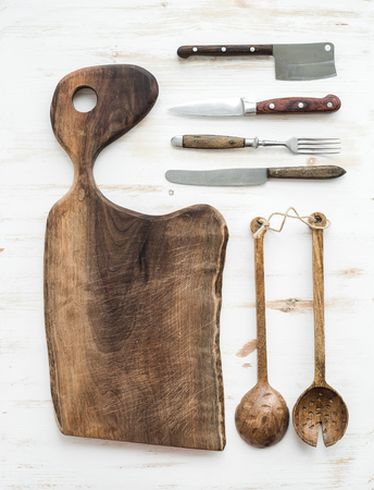 Kitchen-ware set. Old rustic chopping board made of walnut wood, knives, fork and salad spoons on a white background, top view