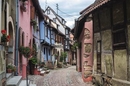 Straße mit Fachwerk mittelalterlichen Häusern in Eguisheim Dorf entlang der berühmten Weinstraße im Elsass, Frankreich Standard-Bild - 46984566