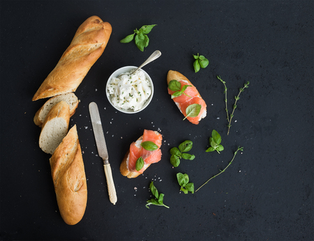 Salmon, ricotta and basil sandwiches with baguette over black grunge background. Top view, copy space