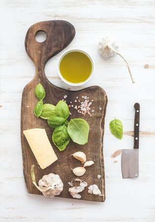 garlic: Pesto sauce cooking set. Fresh basil, olive oil, parmesan cheese and garlic on rustic walnut chopping board over white wooden backdrop, top view