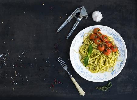pasta: Espaguetis de pasta con salsa de pesto, albahaca, ajo, tomates cherry-horneados en la mesa del grunge oscuro, vista desde arriba, copia espacio
